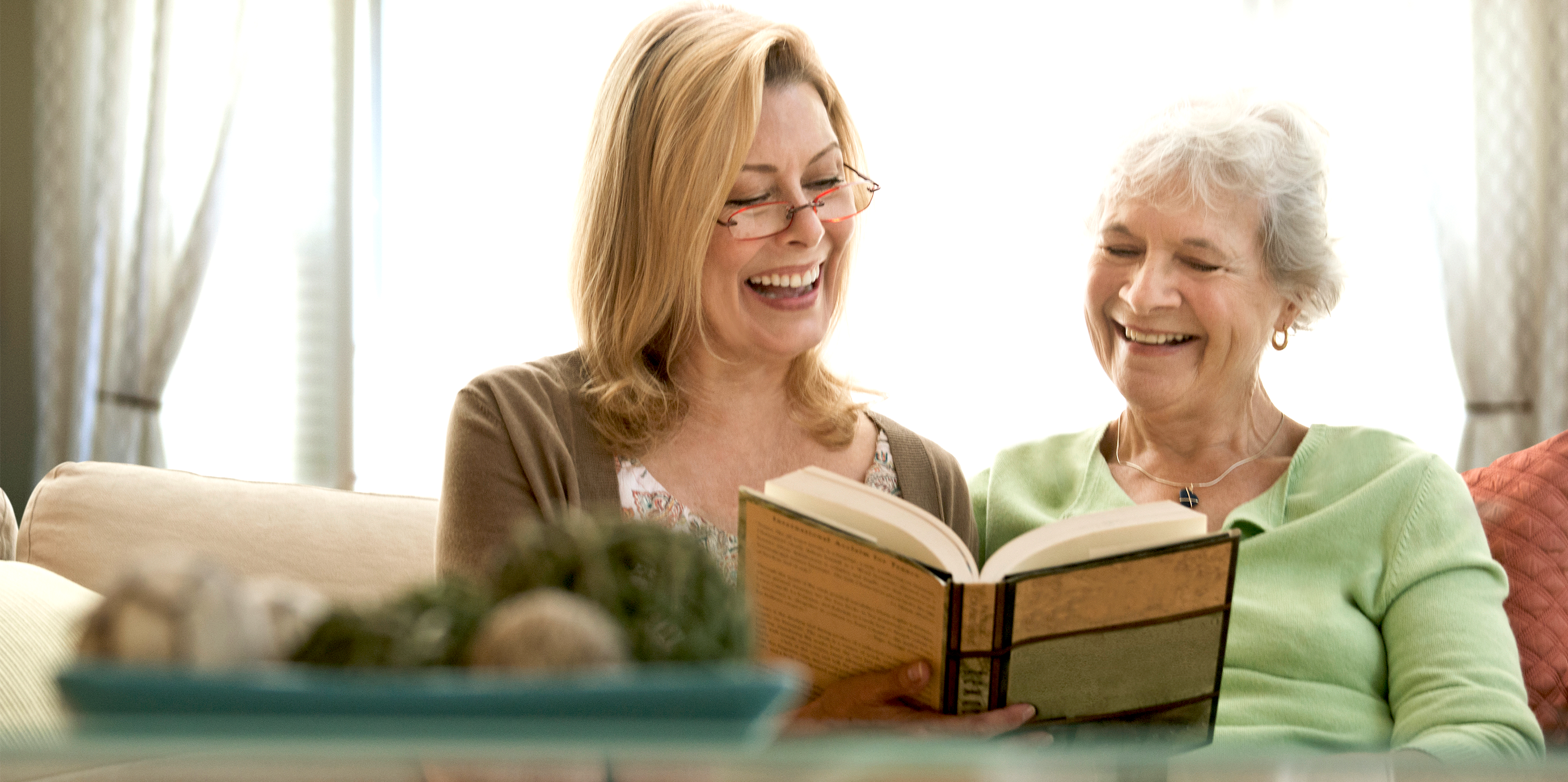 Aide with elder senior woman reading together, primary caregiver support, private duty.