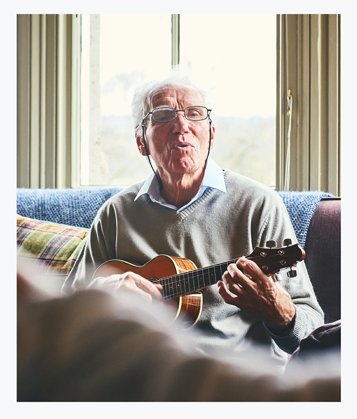 Older gentleman reminiscing playing older songs on a guitar in his spacious luxurious assisted living apartment