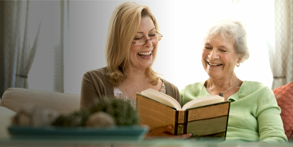 Private aide care giver reading to senior resident at home care