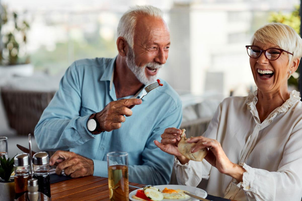 Senior living couple enjoying gourmet meal in independent restaurant.