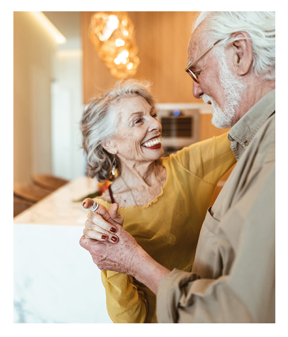 Senior couple dancing in their spacious luxurious independent living apartment with views.