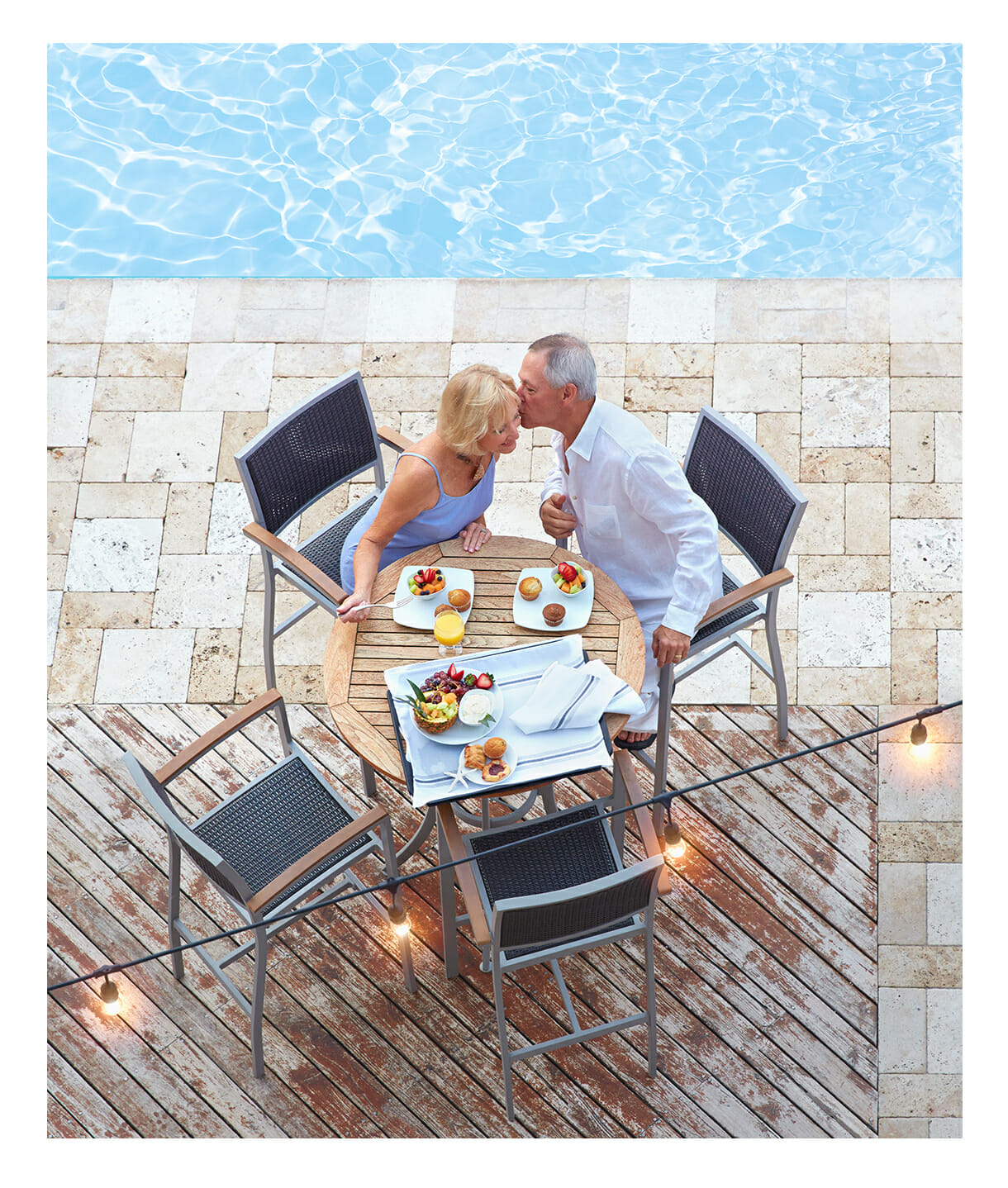Pool side outdoor dining with senior couple.