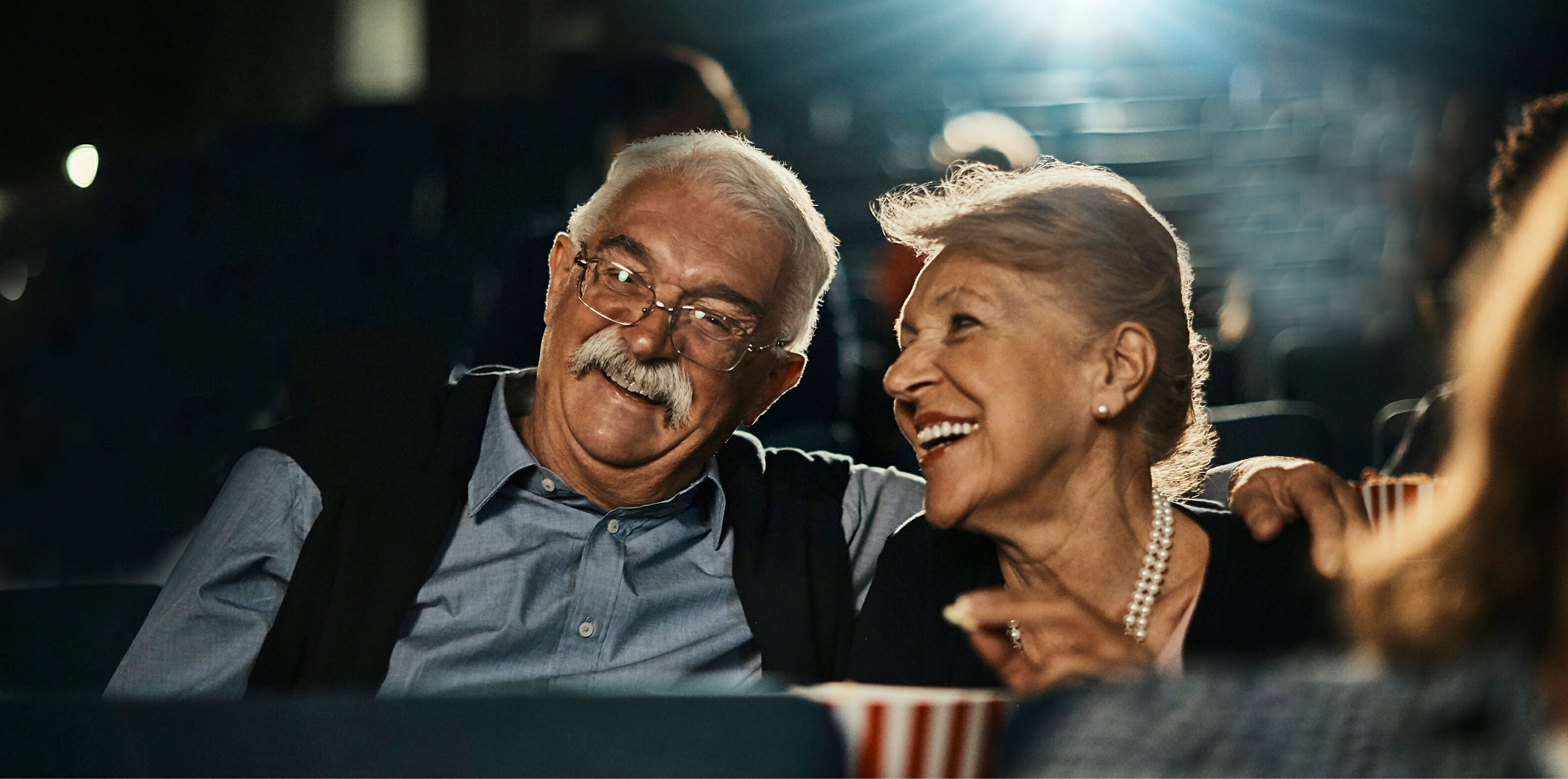 Senior Couple enjoying a movie and eating popcorn