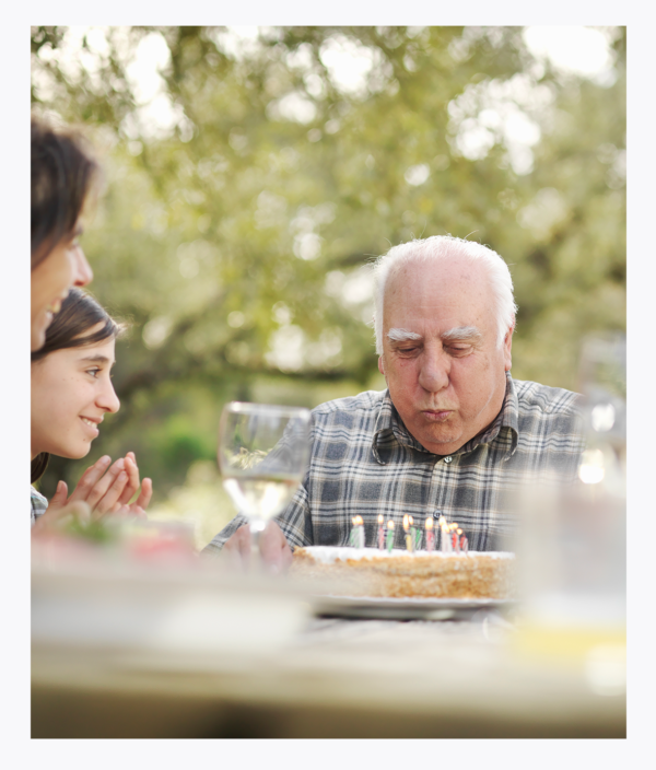 Older male resident celebrating birthday with family while living in senior living community
