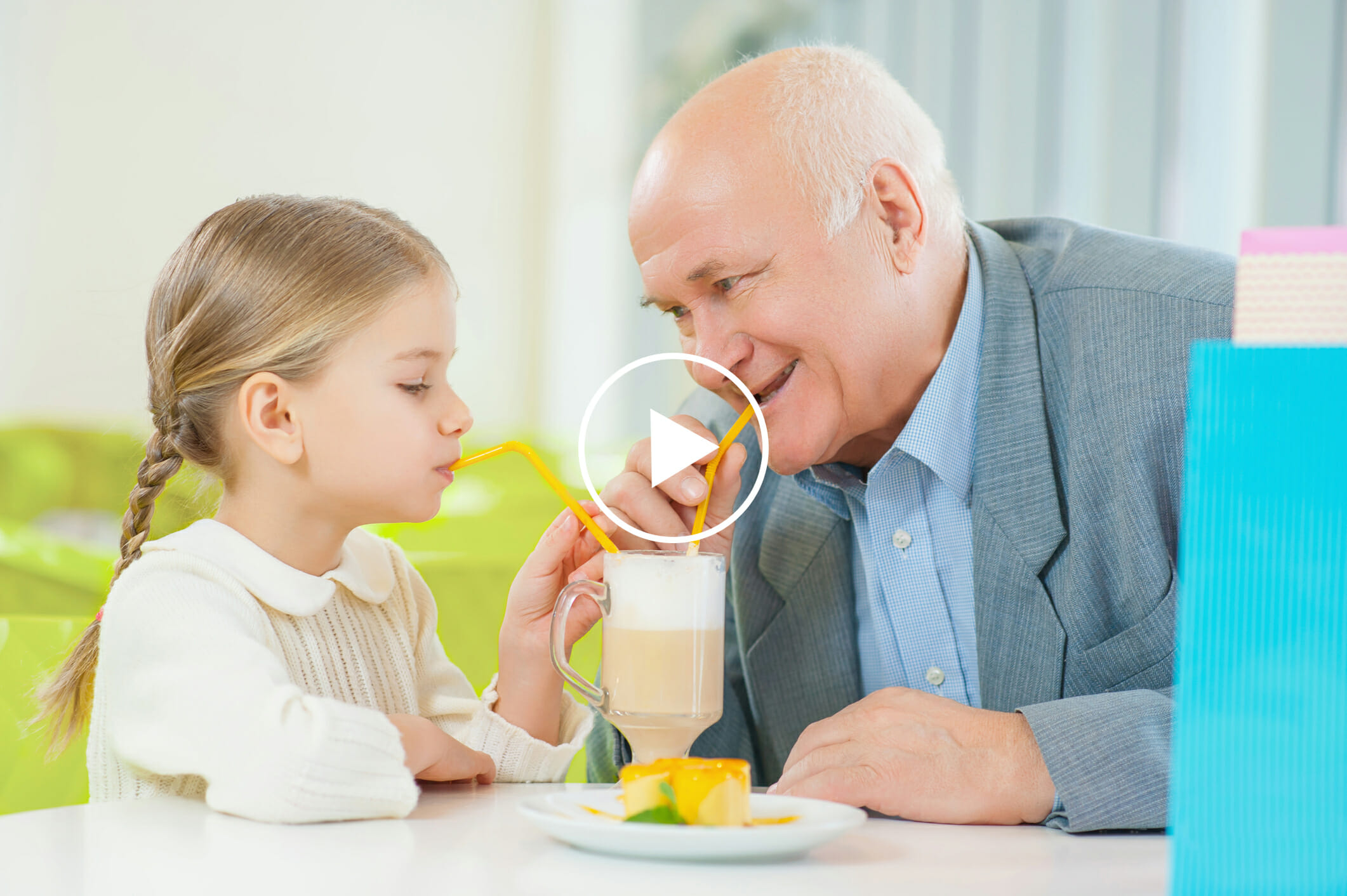 Senior with granddaughter enjoying chocolate milkshake at home private care