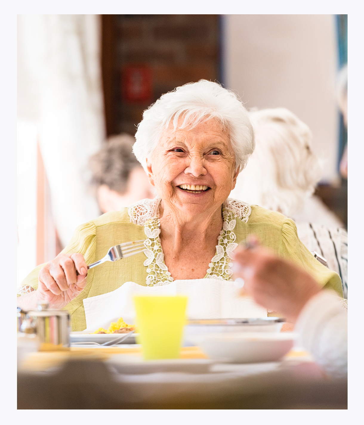 Elderly woman enjoying restaurant-style meal at MorseLife PACE Community Center